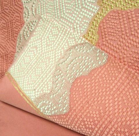 表から裏まで続けて手織りした袋帯は、たれ先が輪になります。